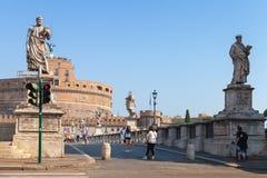 Touristen, die nahe Statuen auf Heiligem Angelo Bridge gehen Lizenzfreie Stockbilder
