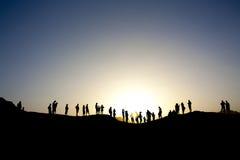 Touristen, die oben auf einen Berg stehen Lizenzfreies Stockbild