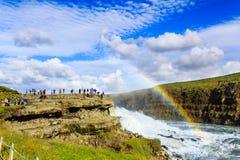 Touristen, die Regenbogen auf Wasserfall in Island aufpassen Stockfoto