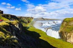 Touristen, die Regenbogen auf Wasserfall in Island aufpassen Stockbilder