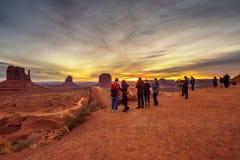 Touristen, die Sonnenaufgang über Monument-Tal aufpassen lizenzfreie stockbilder