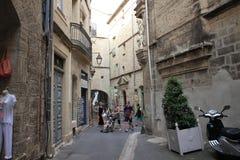 Touristen, die in die Straße der touristischen Stadt von Pezenas, Herault in südlichem von Frankreich gehen Stockfotografie