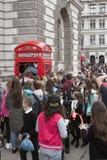 Touristen drücken in traditionellen britischen Telefonkasten zusammen Lizenzfreie Stockfotografie