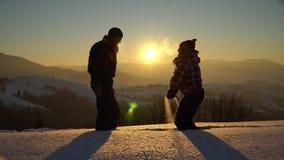 Touristen ein Mann und eine Frau im Winter auf einem schneebedeckten Berg werfen Schnee oben Sie sprangen fröhlich, Händchenhalte stock footage