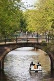 Touristen in einem Feilbietungsboot im Amsterdam-Kanalgurt, die Niederlande Stockfotos