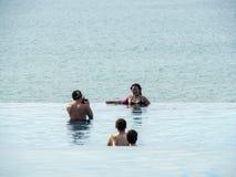 Touristen in einem Unendlichkeitspool mit Ozeanhintergrund stockfoto