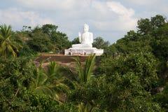 Touristen an einer Skulptur des sitzenden Buddhas auf Ambasthala-Berg Mikhintale, Sri Lanka Lizenzfreie Stockbilder