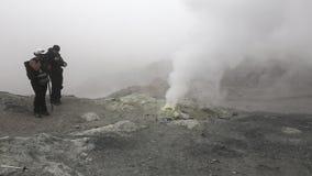 Touristen fotografierten die rauchende Fumarole im aktiven Vulkan des Kraters stock video footage