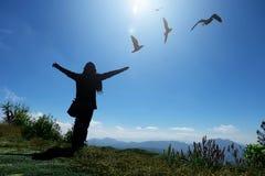 Touristen-Frau in einer Strickjackenstellung auf der Klippe, mit den angehobenen Händen und dem Schauen zum Himmel und zum Berg m stockbilder