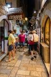 Touristen gehen am Abend durch schmale Straße der alten Stadt, Budva, Montenegro Lizenzfreie Stockfotos