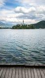 Touristen gehen Bootfahrt am Bled See, Hintergrund ist Insel von Bled, von ausgeblutetem Schloss auf Klippe mit Julian Alps und v Lizenzfreie Stockbilder