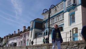 Touristen gehen entlang den Rand der Seefront Lyme Regis stock video footage