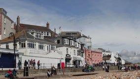 Touristen gehen entlang den Rand der Seefront Lyme Regis an einem sonnigen Frühlingstag stock video footage