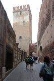 Touristen gehen entlang die Straße, die zu Ponte Scaligero in Verona führt lizenzfreie stockfotos