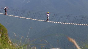 Touristen gehen entlang eine Hängebrücke über einem Abgrund stock footage
