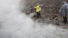Touristen gehen und fotografierend im aktiven Vulkan des Kraters stock video footage