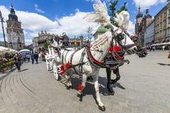 Touristen genießen eine Kutschfahrt am Marktplatz in Krakau Stockfoto