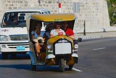 Touristen genießen Reise durch das Motorradtaxi, bekannt, als Cocos, an Malecon-Allee in Havana, Kuba mit einem Taxi fahren lizenzfreies stockfoto