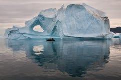 Touristen im aufblasbaren Gummiboot vor verwittertem Eisberg, Scoresby Sund, Grönland stockfoto