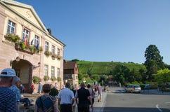 Touristen im Dorf Riquewihr in Elsass in Frankreich Stockbilder