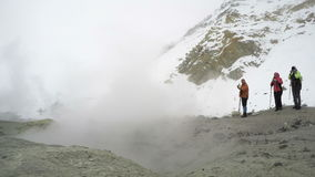 Touristen im Krater des Vulkanfotografierens der aktiven Fumarole stock video footage