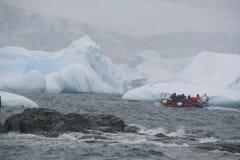 Touristen im Tierkreis ablandig unter Eisbergen stockfotografie