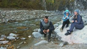 Touristen kampieren nahe dem Fluss Installationslagerofenbrenner Propanbrennstoff, Lagermatch, kampierender Ofen der Windschutzsc stock video footage