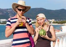 Touristen mit Cocktail auf Damm nahe dem Meer Stockbild