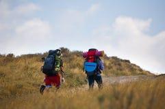Touristen mit den Rucksäcken, die aufwärts gehen Lizenzfreies Stockfoto