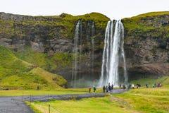 Touristen nahe Seljalandsfoss-Wasserfall in Island Lizenzfreies Stockfoto