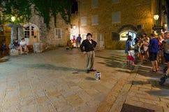 Touristen passen Künstler ` s Leistung auf Abendstraße der alten Stadt, Budva, Montenegro auf Stockbild