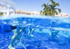 Touristen que hace aeróbicos de la aguamarina en las bicicletas estáticas en hotel tropical de la piscina foto de archivo libre de regalías