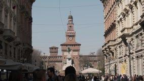 Touristen schlendern entlang über Dante in Mailand und im Sforza-Schloss im Hintergrund stock video