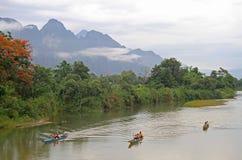 Touristen schwimmen in Kanus fast Vang Vieng Lizenzfreies Stockfoto