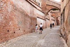 Touristen in Sibiu gehend nahe einer Backsteinmauer Lizenzfreie Stockbilder