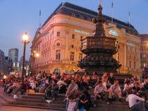 Touristen sitzen auf den Schritten des Erinnerungsbrunnens in Piccadilly-Zirkus Stockbild