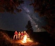 Touristen sitzen auf Klotz durch Feuer unter Tannenbäumen auf dem Hintergrund des Himmels gestreut mit Sternen Stockbild