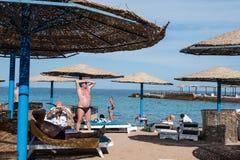 Touristen sonnen sich auf dem Strand in Hurghada in Ägypten Stockfotos