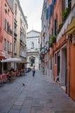Touristen stehen in einem Café auf der Straße unter alten Gebäuden in VENEDIG, ITALIEN still lizenzfreies stockbild