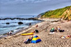 Touristen und Besucher Portwrinkle setzen Whitsand-Bucht Cornwall England Vereinigtes Königreich in buntem HDR auf den Strand Stockfotos