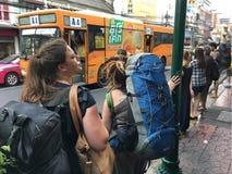 Touristen und Einheimische an der Bushaltestelle in Bangkok Stockfotos