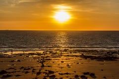Touristen und Einheimische, die bei Sonnenuntergang auf dem Strand in Broome und enyoing Sonnenuntergang, mit einem großen Schiff lizenzfreie stockfotografie