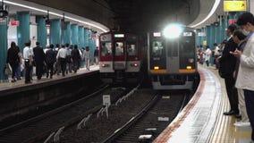 Touristen und japanische Pendler, die auf einen Nahverkehrszug ankommt bei Kintetsu Nara Station warten stock footage