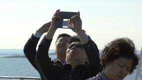 Touristen von China, das enthusiastisch Bilder der Seemöwen die Fähren akzeptiert stock video