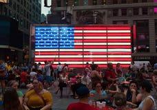 Touristen vor einer elektronischen amerikanischen Flagge im Times Square Lizenzfreies Stockfoto