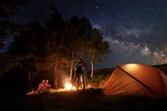 Touristen während der Nacht des Kampierens um Lagerfeuer nahe Zelt unter sternenklarem Himmel auf Hintergrund von Bäumen Stockfoto