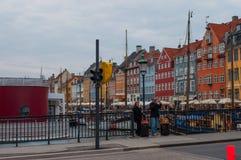 Touristen, welche die Ansicht über eine Brücke in Nyhavn-Kanal in Denma genießen lizenzfreie stockbilder
