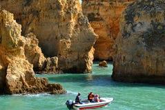 Touristen, welche die Ansicht der großartigen Felsformationen von einem Boot genießen Stockfotos
