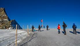 Touristenbesuch Jungfrau-Spitze mit Schweizer Flagge stockfotos