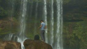 Touristennehmen ruft von den Rucksackständen auf Felsen an stock footage